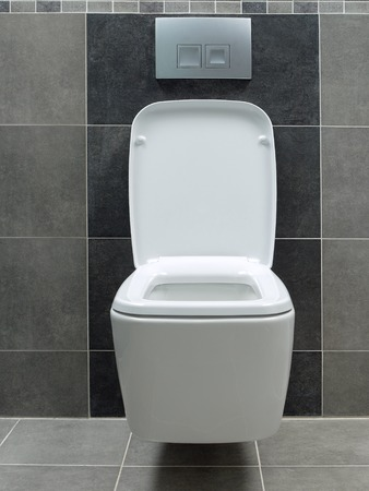 toilet bowl: Wall mounted white ceramic toilet in gray tiled bathroom