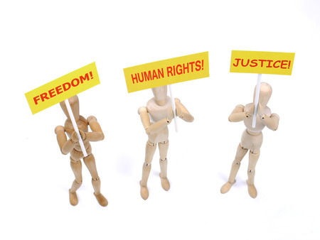 protestor: Three wooden dummies as demonstrators holding placads saying - Freedom, Human Rights and Justice shot on white background Stock Photo