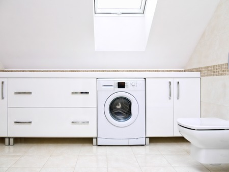Modern bathroom with shiny white cabinets and wash machine Banque d'images