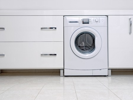 Row of white modern bathroom cabinets with built-in washing machine