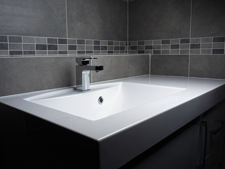 Modern bathroom washbasin with chrome faucet and gray tiling 写真素材