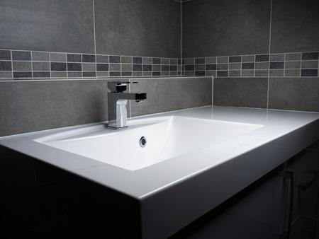 Modern bathroom washbasin with chrome faucet and gray tiling Standard-Bild