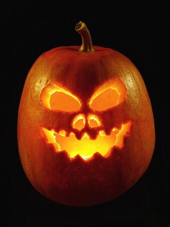 pumpkin face: Lit Jack-o-lantern pumpkin on black background