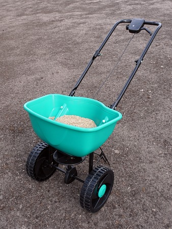 manually: Manually operated seeder filled with grass seeds shot on soil Stock Photo