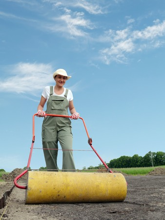 Female gardener leveling soil surface using garden roller photo
