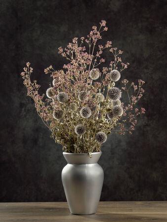 flores secas: Flores silvestres secas ramo en el florero de plata sobre fondo gris oscuro Foto de archivo