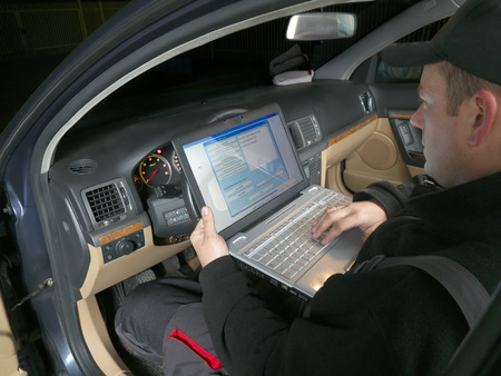 Auto mechanic checking vehicle identification number of the car using laptop hooked up to the car onboard computer Banque d'images