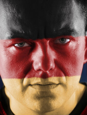 Closeup of young German supporter face painted with national flag colors photo
