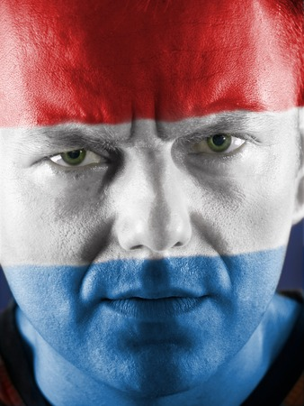 supporter: Closeup of young Dutch supporter face painted with national flag colors