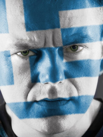 Closeup of young Greek supporter face painted with national flag colors