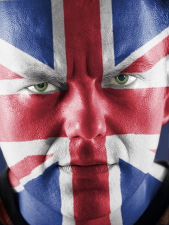 Closeup of young UK supporter  face with painted national flag colors