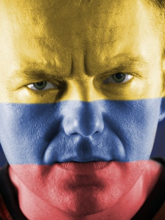 colombian: Closeup of young colombian supporter face painted with national flag colors Stock Photo