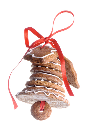bell shaped: Christmas bell assembled from gingerbread shaped cookies and tied with red ribbon shot over white  background