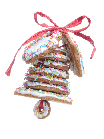 bell shaped: Christmas bell assembled from gingerbread shaped cookies and tied with red ribbon shot over white blue background