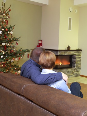 Romantic couple sitting on sofa near christmas tree looking at the lit fireplace photo
