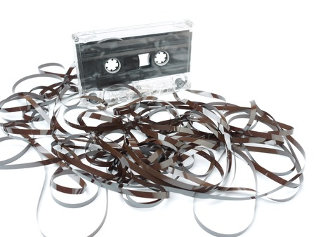 cassette tape: Old audio cassette tape pulled out and tangled on white background