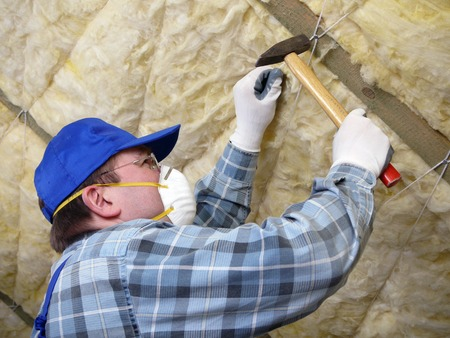 insulate: Worker thermally insulating a house attic using mineral wool Stock Photo
