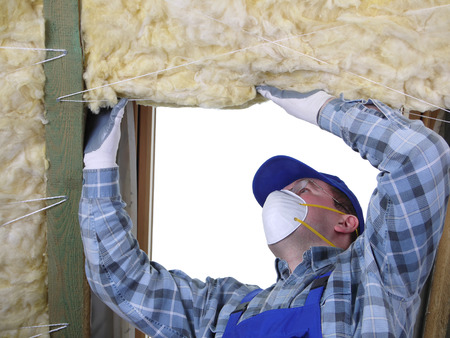 building material: Worker thermally insulating a house attic using mineral wool Stock Photo