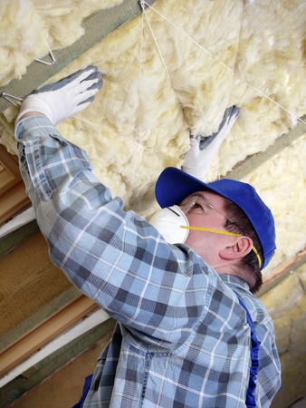 rafter: Worker thermally insulating a house attic using mineral wool Stock Photo