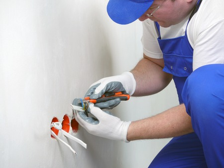 wall socket: Electrician stripping electrical wires for wall socket