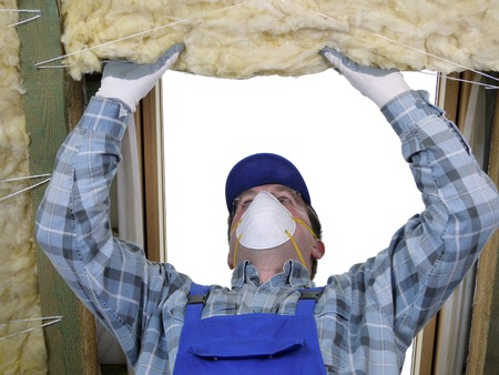 Worker thermally insulating a house attic using mineral wool Imagens