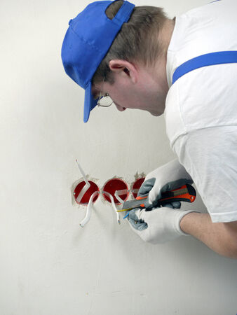 Electrician stripping electrical wires for wall socket  photo