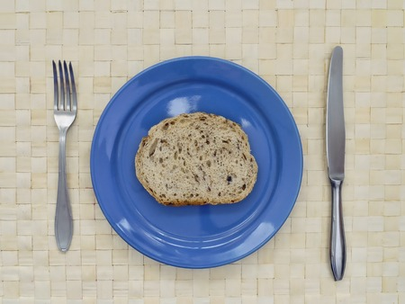 calories poor: Slice of bread on blue plate with fork and knife Stock Photo
