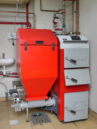 House boiler room with coal-fired central heating furnace system photo
