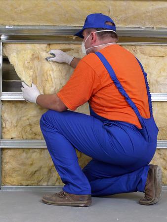 materiales de construccion: Trabajador de la construcción termoaislante ático casa con lana mineral Foto de archivo