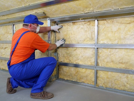 Construction worker thermally insulating house attic with mineral wool Stock Photo - 26589542
