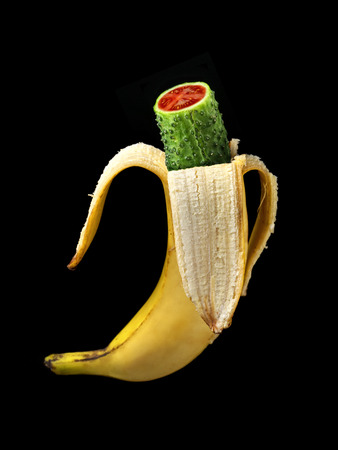 Hybrid of banana, green cucumber and tomato as GMO concept shot over black photo