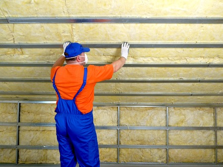 Construction worker thermally insulating house attic with mineral wool Stock Photo - 26775475
