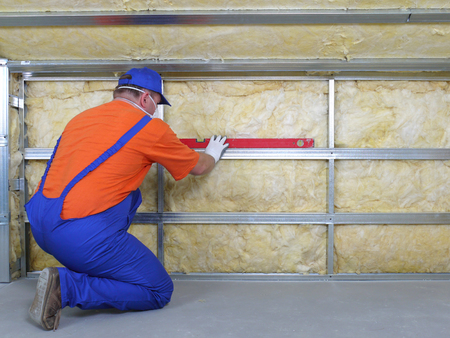 Construction worker thermally insulating house attic with mineral wool photo