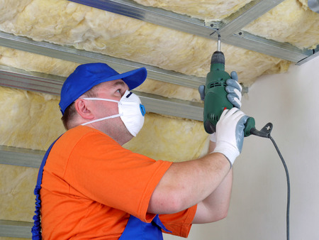 rockwool: Construction worker thermally insulating house attic with mineral wool
