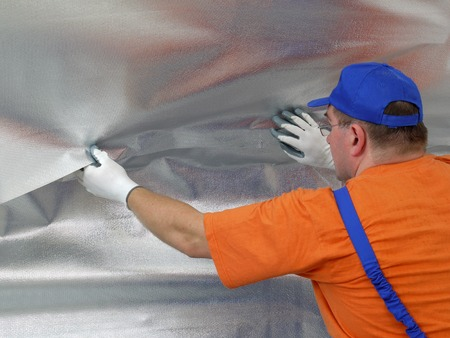 Construction worker affixing vapour insulation foil under thermally insulated attic surface 写真素材