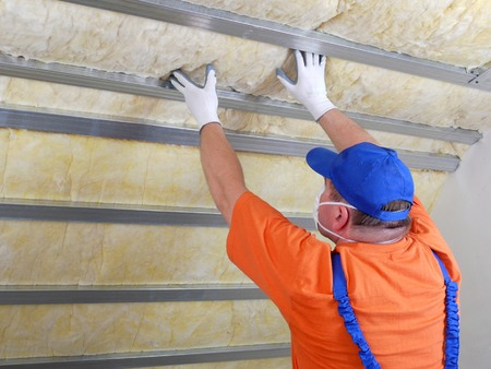 minerals: Construction worker thermally insulating house attic with mineral wool
