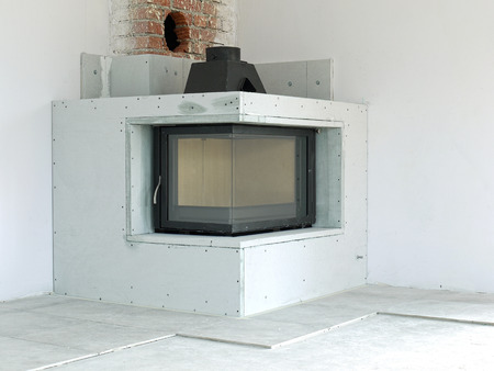 Modern corner wood-fired fireplace under construction photo