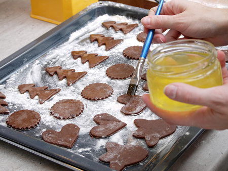 egg white: Christmas gingerbread cookies cut out from raw pastry being brushed with egg white