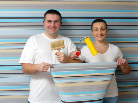 Young happy couple posing against papered wall holding some basic wallpapeping tools photo