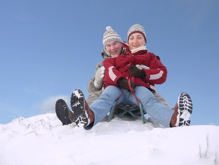 hillock: Young couple going down the hill on sledge in winter time