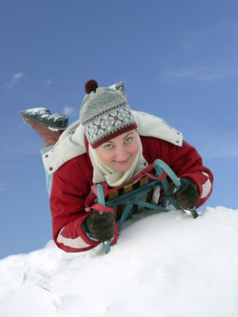 hillock: Young woman smiling going down the hill belly-flop in winter time