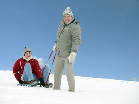 Young man tugging his wife sitting on sledge on snow over blue sky photo