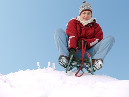 hillock: Young woman smiling going down the hill on sledge