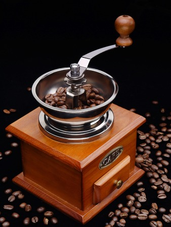 Manual coffee grinder filled with coffee beans shot over black background photo