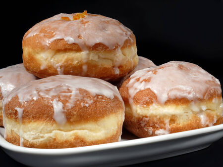 surfeit: Polish donuts with icing over black background