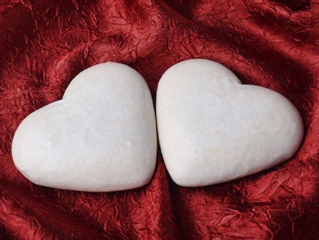 Two heart-shaped gingerbread cakes on scarlet fabric photo