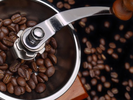 Closeup of manual coffee grinder filled with coffee beans photo