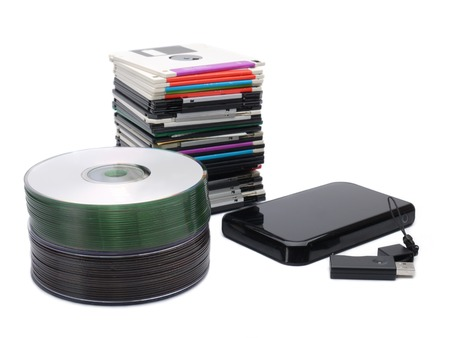 diskette: Pile of floppy disks, cd-roms, external hard drive and pen drive over white