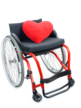 invalidity: Red heart pillow on wheelchair isolated on white background
