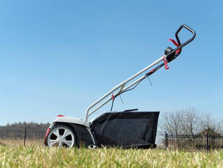 aeration: Lawn scarifier shot on backyard lawn over the sky